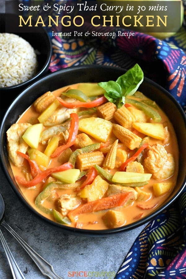 mango chicken curry in black bowl with side of rice