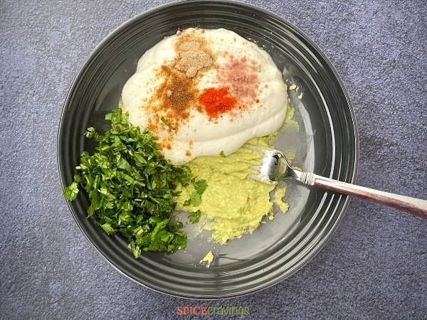 mashed avocado, yogurt, indian spices, chopped cilantro in stoneware bowl with fork
