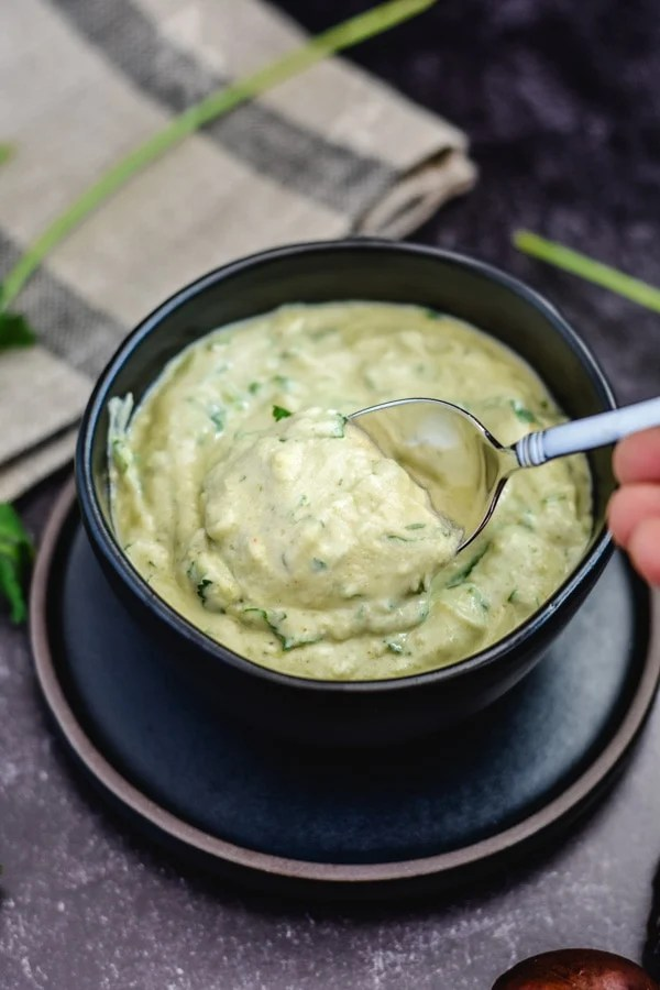indian guacamole sauce in black bowl with spoon