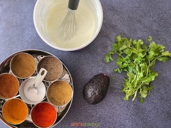 indian spices, avocado, cilantro, yogurt with whisk
