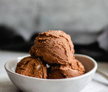 three scoops homemade chocolate ice cream in white bowl