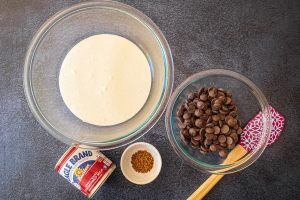 chocolate chips and heavy cream in glass mixing bowls with spatula and can of condensed milk