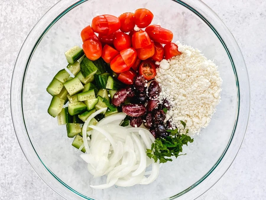 diced cucumbers, tomatoes, onions, olives, feta cheese, herbs in glass bowl