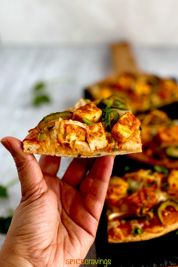 hand holding indian flatbread pizza with marinated paneer cheese and veggies on black board