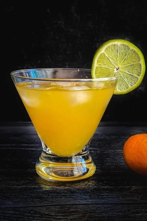 An orange skinny margarita cocktail garnished with a lime wheel