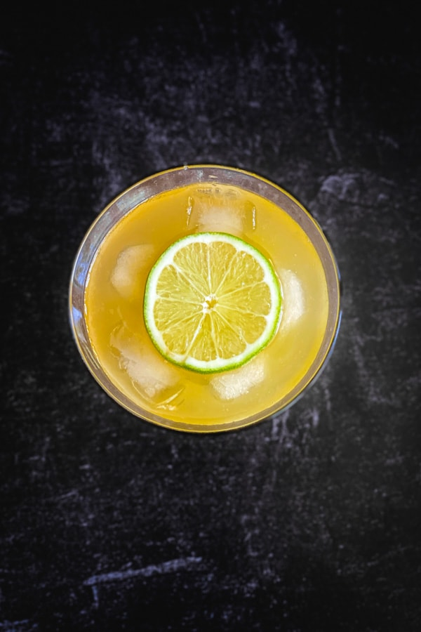 Lime slice placed on ice in an orange drink