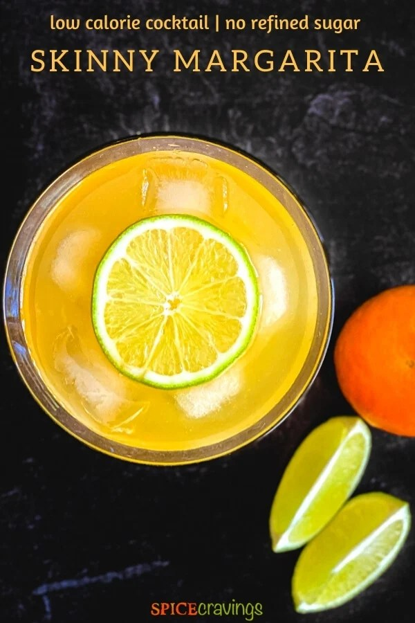 Top view of an orange drink garnished with a lime wheel