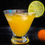 Orange drink in a glass garnished with a lime wheel