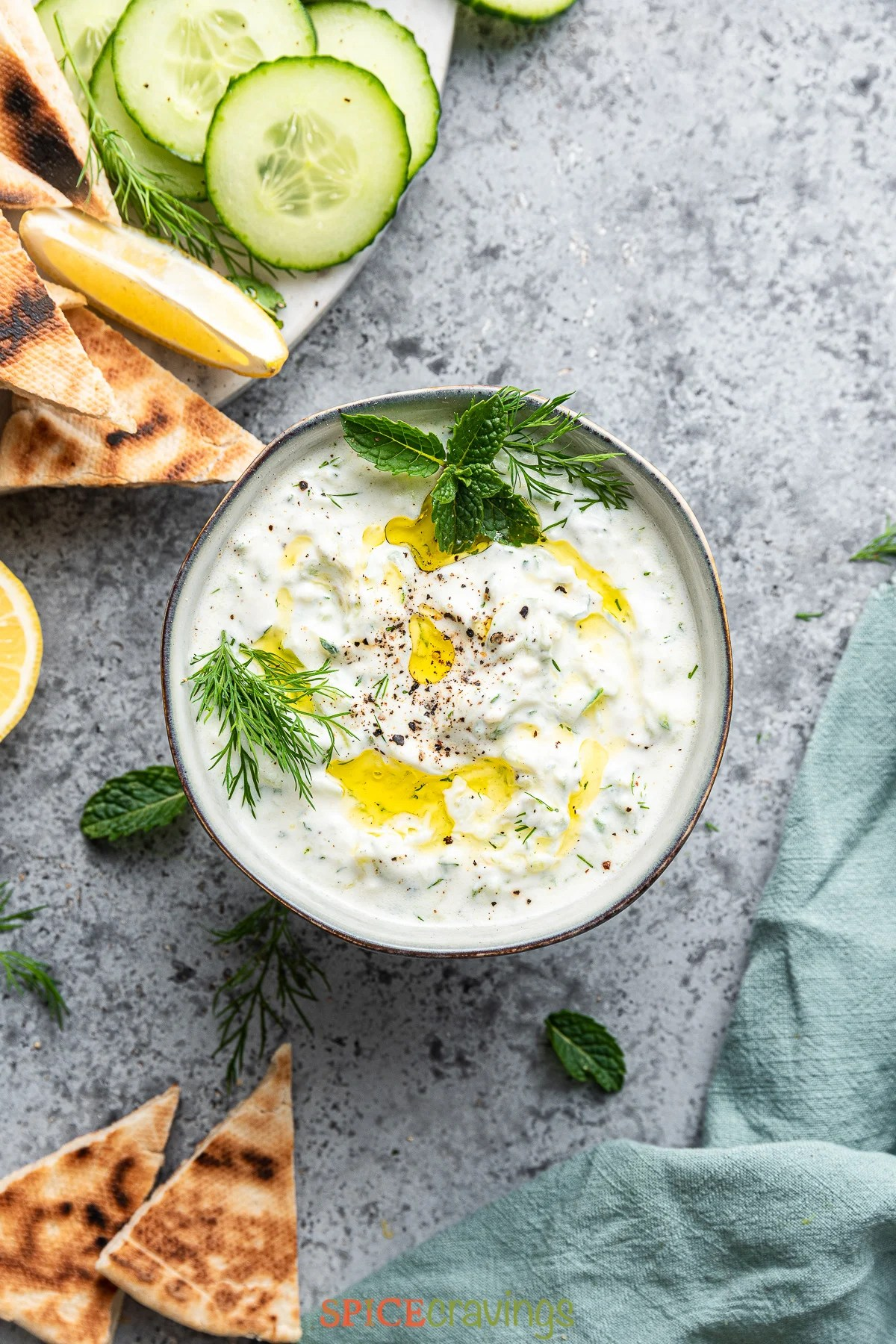 homemade tzatziki sauce in black bowl with fresh vegetable on black plate