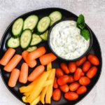 Greek tzatziki dip recipe in black bowl with fresh vegetables pinterest graphic