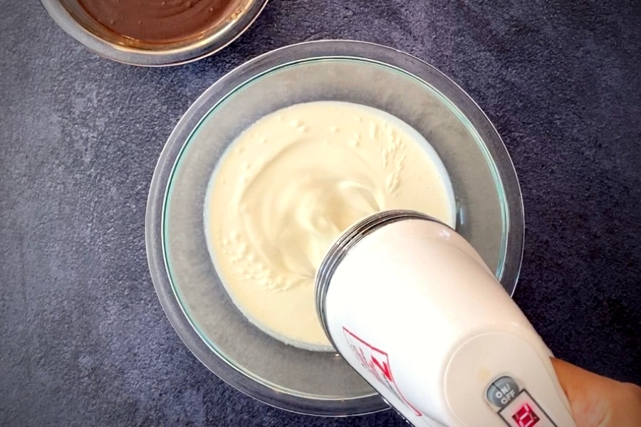 electric mixer whipping cream in glass bowl