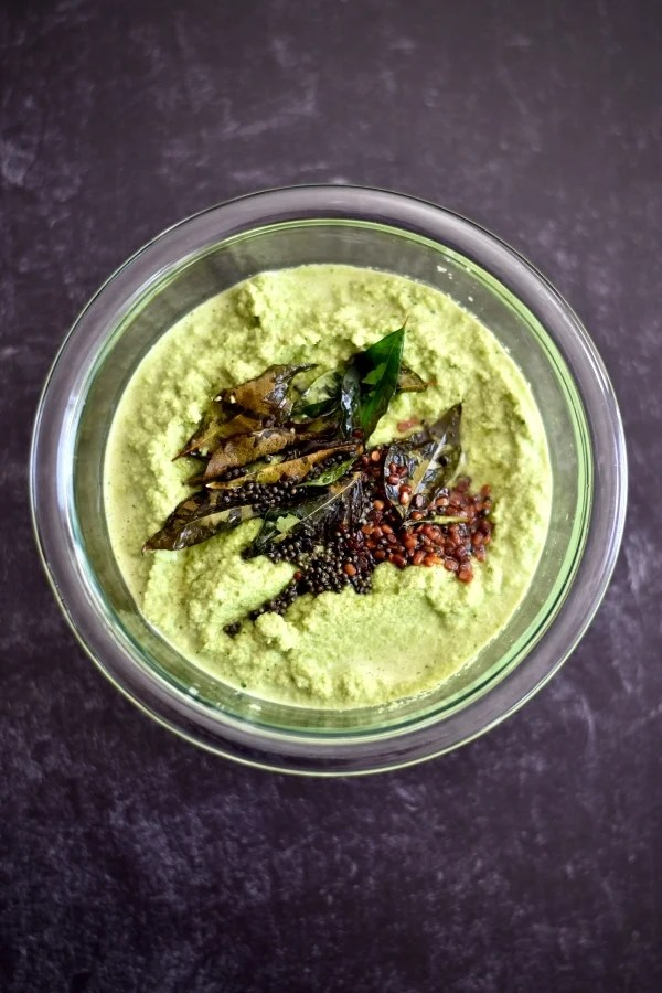 cilantro chutney topped with hot tadka in glass bowl