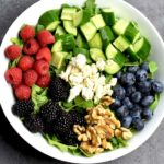 arugula, cucumbers, raspberries, blueberries, blackberries, walnuts, feta in white bowl