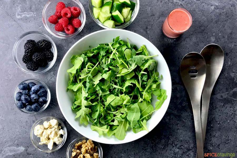 arugula in white bowl with cucumbers, berries, feta, walnuts in separate glass bowls