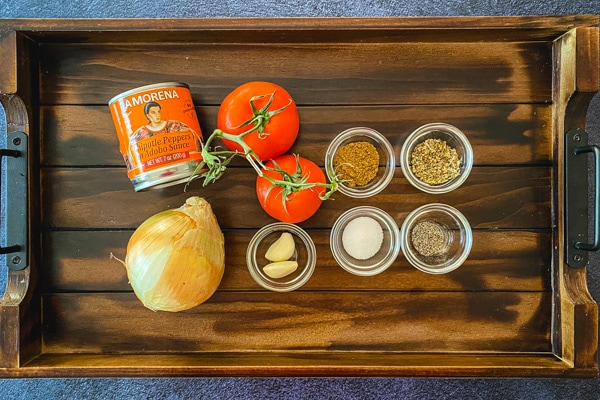 onion, canned chipotle peppers, tomatoes, garlic, spices in small bowls on wooden board