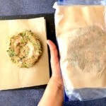 two hands wrapping chicken burger in parchment paper