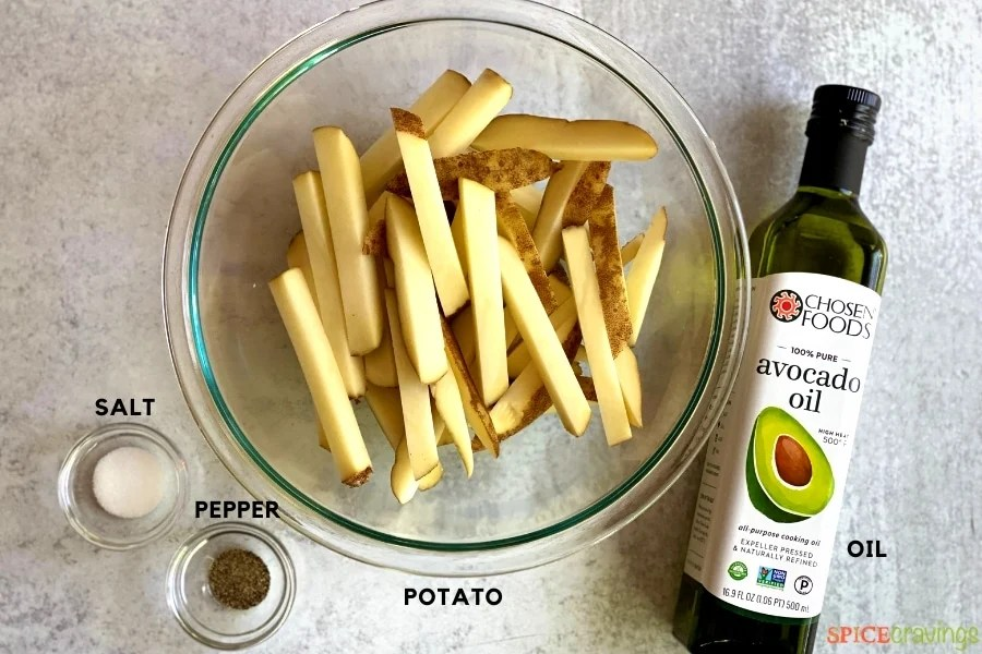 sliced potatoes in glass bowl, avocado oil jar, salt and pepper in two small bowls