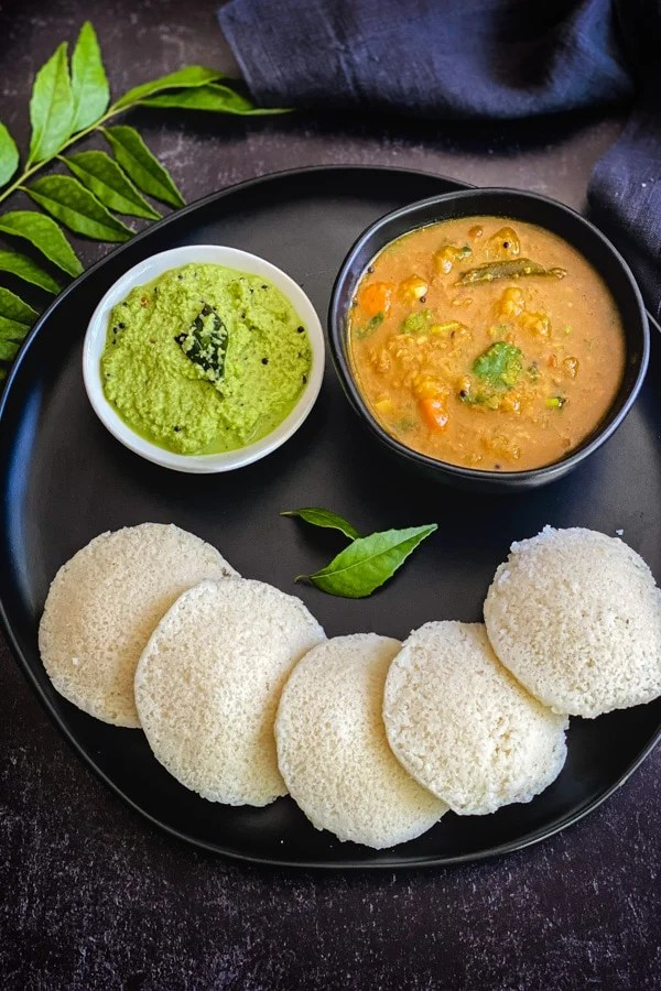 steamed rice cakes on black plate with sambar and coconut chutney