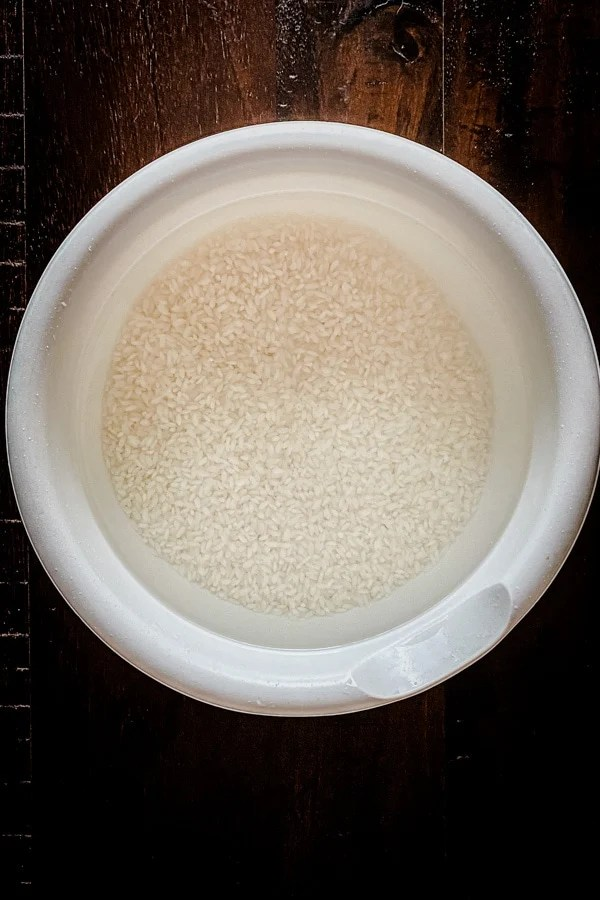idli rice soaking in water in white bowl