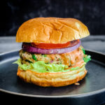 indian spiced chicken burger with lettuce, tomato, onion, sriracha mayo on bun on black plate