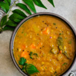 instant pot sambar recipe in gray bowl with curry leaves on the side