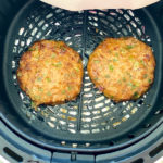 two chicken burger patties cooking in air fryer basket
