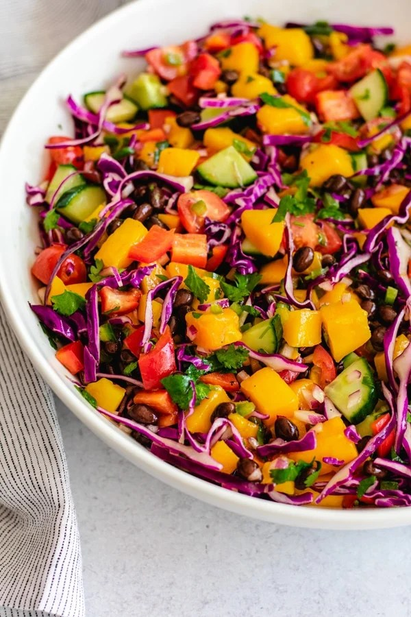 mango and black bean salad with fresh vegetables in white bowl