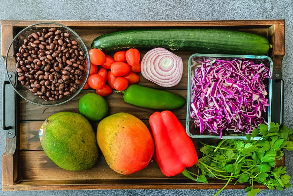 black beans, tomatoes, cucumber, red onion, sliced red cabbage, lime, mangoes, pepper, cilantro on wooden board