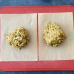 two ground chicken taco burger mix on parchment paper on cutting board