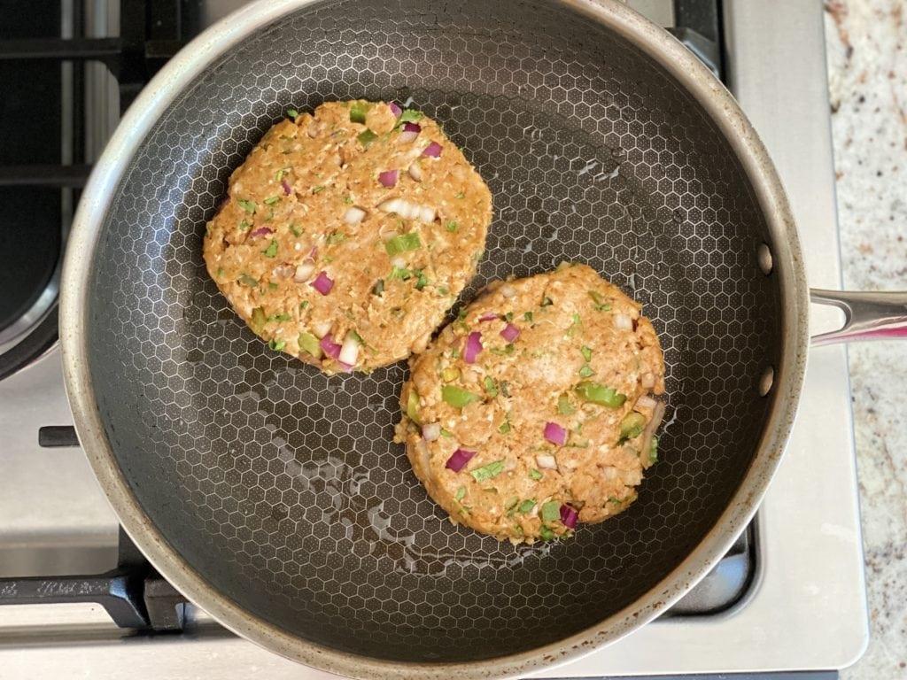 two burger patties cooking in nonstick skillet