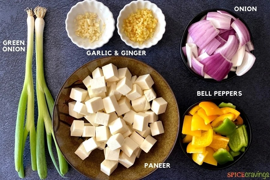 paneer cubes in brown bowl, scallion, minced garlic and ginger, chopped red onion and bell peppers
