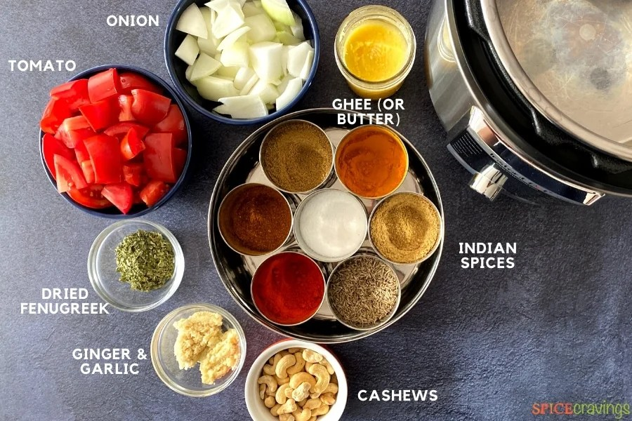 Ingredients for Paneer Tikka Masala laid on a gray background