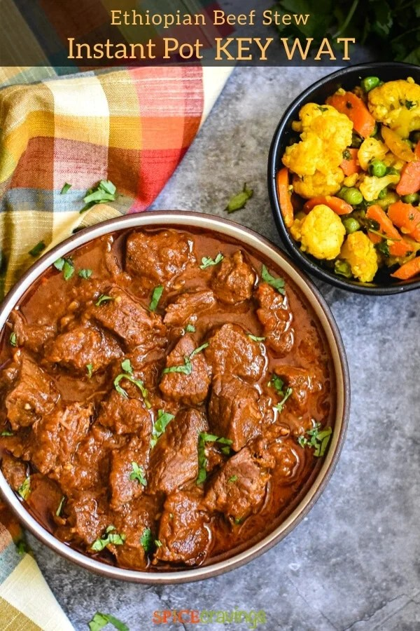A bowl of beef stew next a bowl of assorted veggies