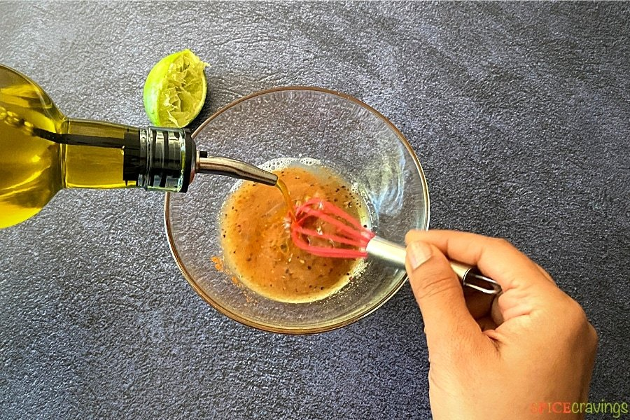 pouring olive oil into small glass bowl while whisking