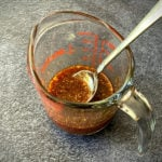 Asian sauce in measuring cup with spoon