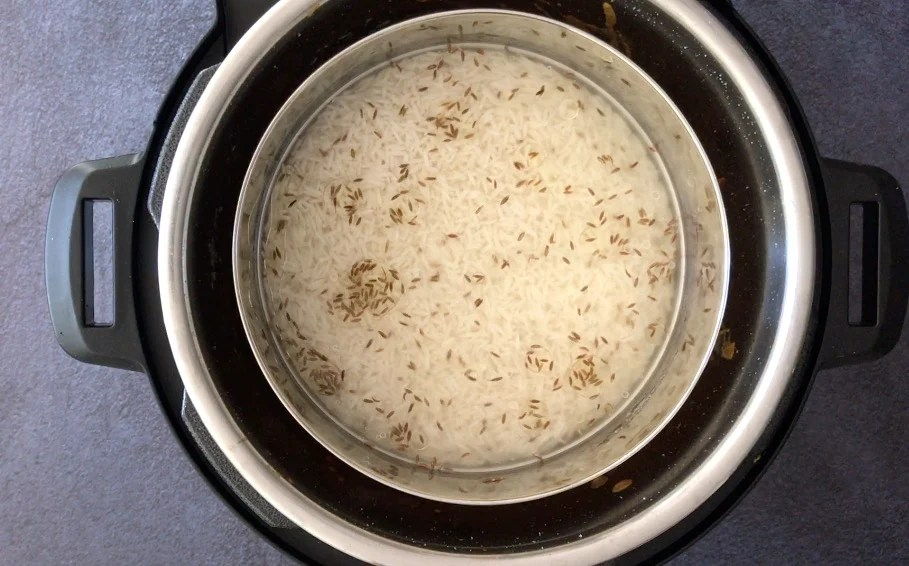 Adding a small bowl of rice, water and cumin seeds in the Instant Pot