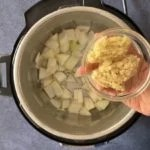 Adding ginger and garlic to the pot