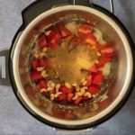Adding tomato, spices and cashews to the pot