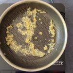 minced garlic and ginger in stainless steel skillet on hot plate