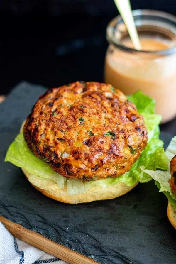 taco burger patty on hamburger bun with lettuce and sriracha mayo on side