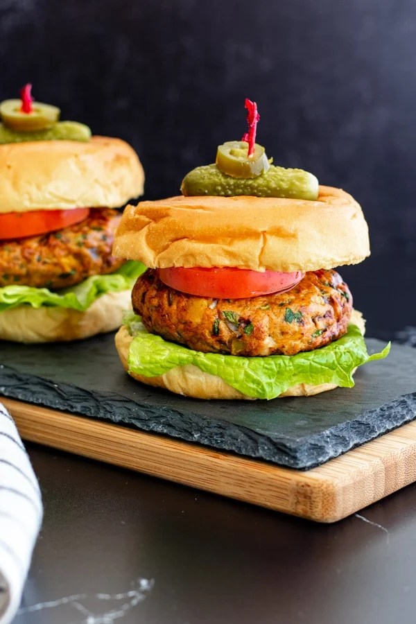 two mexican chicken burgers on buns with lettuce, tomato and skewered with pickle