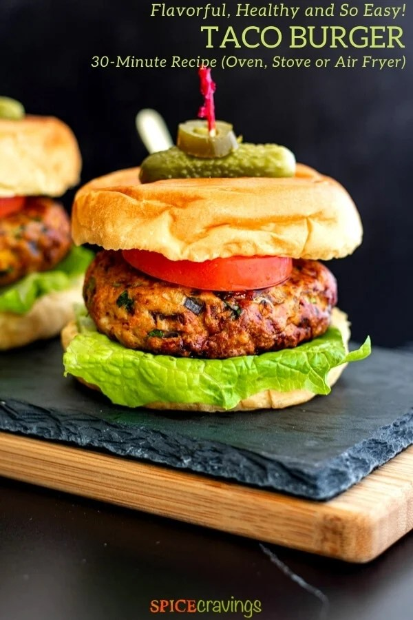 mexican chicken burger on buns with lettuce, tomato and skewered with pickle