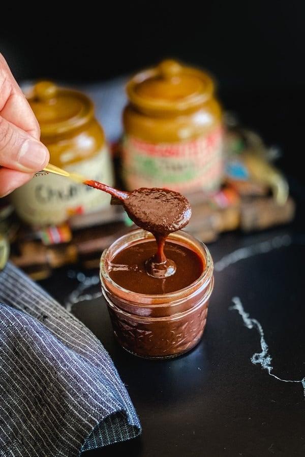 Spoon dipped in a jar of tamarind sauce