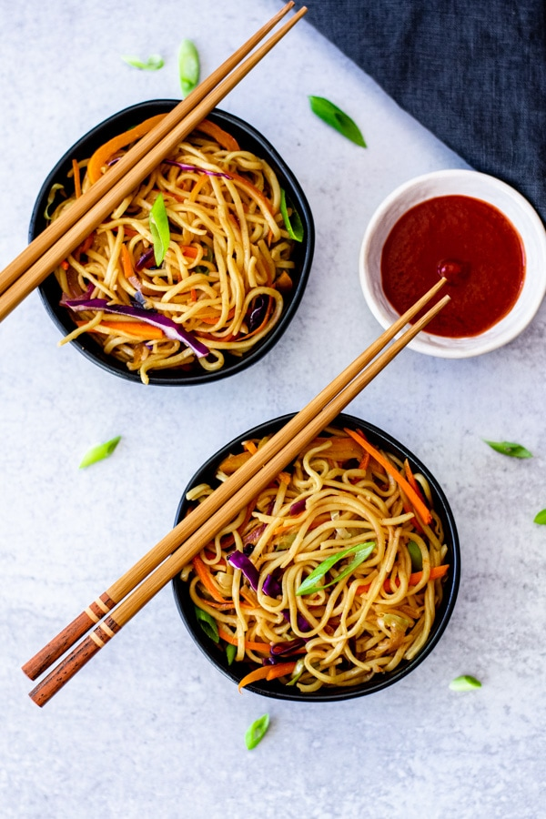 vegetable chow mein recipe in two small black bowls with chopsticks and sauce on side