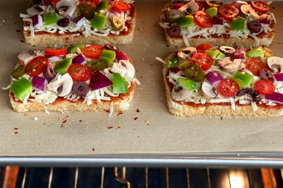 slices of bread, cheese and vegetable toppings on parchment-lined baking sheet in oven