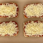 shredded cheese and tomato sauce on four slices of bread on parchment-lined baking sheet