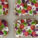 fresh vegetables, cheese and tomato sauce on bread slices on parchment paper