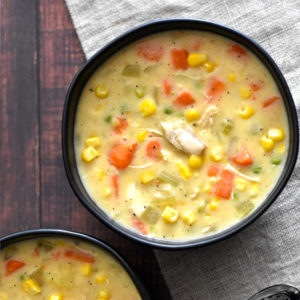 A black bowl with chicken and corn chowder with carrots and celery