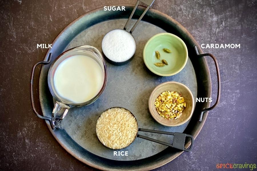 milk, rice, sugar, green cardamom pods, pistachios in bowls
