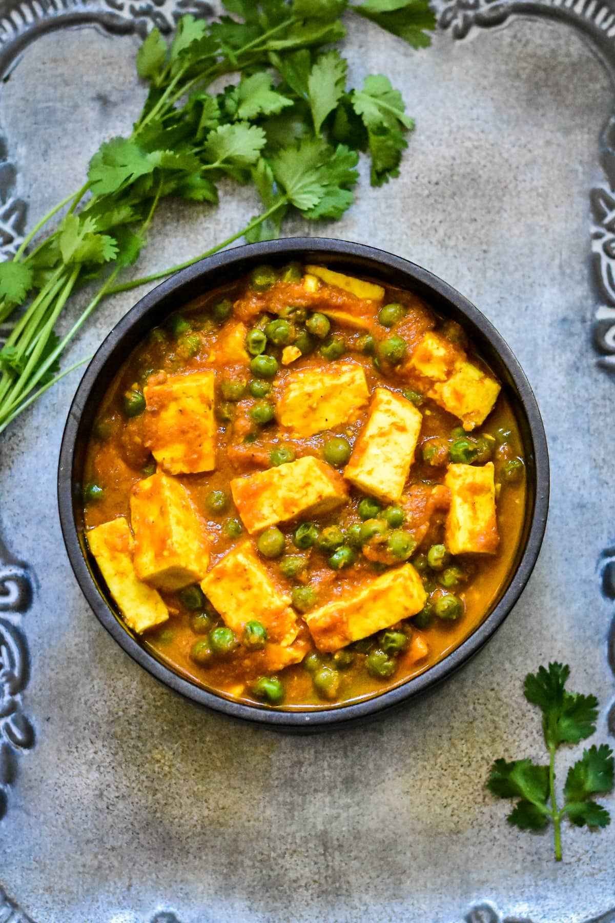 paneer and pea curry in black bowl with cilantro sprigs on silver platter